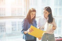 2 женщины обсуждая рабочий план в офисе Большое яркое окно позади Стоковая Фотография