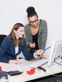 2 женщины обсуждают перед компьютером на офисе Стоковые Фото