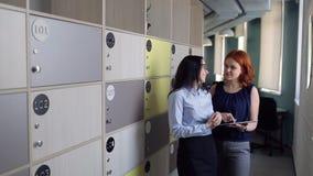 2 женщины обсуждают что-то в офисе около клеток хранения сток-видео