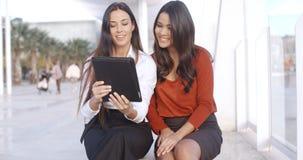 2 женщины обсуждая информацию на таблетке Стоковые Фото