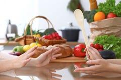 2 женщины обсуждая новое меню в кухне, конец вверх Человеческие руки 2 людей жестикулируя на таблице среди Стоковые Изображения