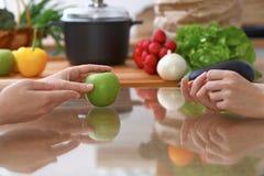 2 женщины обсуждая новое меню в кухне, конец вверх Человеческие руки 2 людей жестикулируя на таблице среди Стоковые Фотографии RF