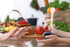 2 женщины обсуждая новое меню в кухне, конец вверх Человеческие руки 2 людей жестикулируя на таблице среди Стоковое Изображение