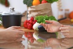 2 женщины обсуждая новое меню в кухне, конец вверх Человеческие руки 2 людей жестикулируя на таблице среди Стоковая Фотография RF