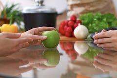 2 женщины обсуждая новое меню в кухне, конец вверх Человеческие руки 2 людей жестикулируя на таблице среди Стоковые Фото
