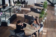 2 женщины обсуждая документы в офисе или кафе Консультант с женщиной Стоковые Фото