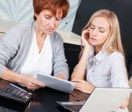 2 женщины обсуждая документы на кухне Стоковое Изображение