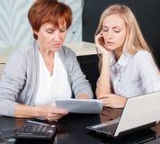 2 женщины обсуждая документы дома Стоковые Изображения RF