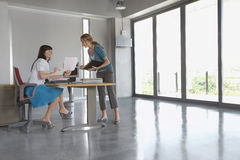 Женщины обсуждая документ на столе в пустом офисе Стоковое Изображение