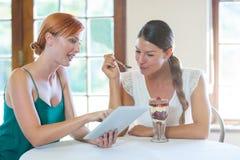 Женщины обсуждая с цифровой таблеткой Стоковые Фото