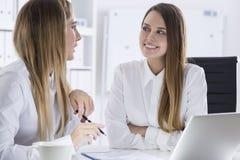 2 женщины обсуждая частные вопросы в офисе Стоковые Фото