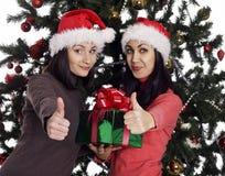 2 женщины около рождественской елки с присутствующей показывая рукой одобренный знак Стоковые Фото