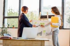 Женщины около chartboard на офисе Стоковая Фотография