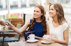 Женщины оплачивая деньги к кельнеру для кофе на кафе Стоковые Фотографии RF
