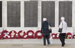 Женщины осматривая венки a бассейна военноморской военный мемориал Плимут Великобритания Стоковые Фотографии RF