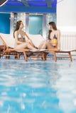 Женщины ослабляя бассейном Стоковые Фото