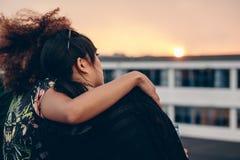 Женщины ослабляя на крыше и смотря заход солнца Стоковое Изображение