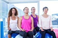 Женщины ослабляя на шариках тренировки с глазами закрыли Стоковое Изображение RF