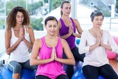 Женщины ослабляя на шариках тренировки с соединенными руками Стоковые Изображения