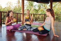 Женщины ослабляя с соком кокоса после занятий йогой Стоковое Изображение RF