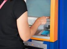 Женщины отжимая машину ATM Стоковые Изображения