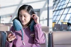 Женщины отправляя СМС на летать мобильного телефона ждать на окно авиапорта стоковое изображение rf