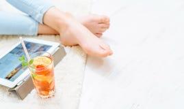 Женщины отдыхают на поле дома и используют таблетку Стоковые Фотографии RF