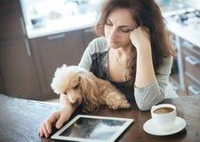 Женщины отдыхают с собакой дома и используют таблетку Стоковые Изображения