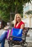 Женщины отдыхая после ходить по магазинам на стенде Стоковые Фотографии RF