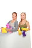 2 женщины очищают что-то с пучком и брызгом внимательно Стоковая Фотография