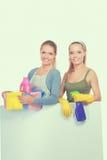 2 женщины очищают что-то с пучком и брызгом внимательно Стоковые Фотографии RF