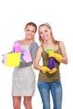 2 женщины очищают что-то с пучком и брызгом внимательно Стоковое Изображение