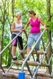 2 женщины, одна беременная, на спорте фитнеса в взбираясь парке Стоковые Изображения