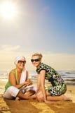 женщины пляжа сидя Стоковая Фотография