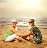 женщины пляжа сидя Стоковые Изображения