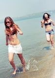 женщины пляжа счастливые играя молодые Стоковая Фотография