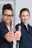 2 женщины показывают большие пальцы руки вверх Стоковые Изображения