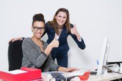 2 женщины показывают их большие пальцы руки вверх Стоковые Фотографии RF