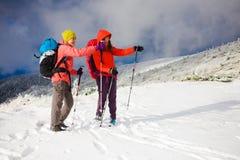 2 женщины показывают путь в горах в зиме Стоковые Фото