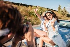 2 женщины показывая знак мира и представляя к фотографу человека Стоковые Фотографии RF
