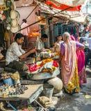 Женщины покупают красочные гирлянды на Стоковое Фото