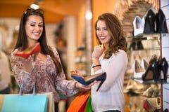 Женщины покупая ботинки в магазине Стоковая Фотография