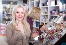 Женщины покупая губную помаду в разделе состава Стоковые Изображения RF