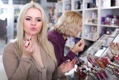Женщины покупая губную помаду в разделе состава Стоковые Изображения