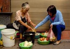 2 женщины покупая и продавая свежие яичка в старом квартале Ханоя, Вьетнама Стоковое Изображение RF