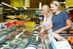 Женщины покупая, который замерли овощи Стоковые Фото