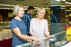 Женщины покупая, который замерли овощи Стоковые Изображения