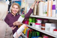 Женщины покупая шампунь Стоковое Изображение