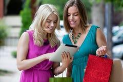 Женщины покупок используя таблетку цифров Стоковые Изображения RF