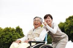Женщины помогли кресло-коляске стоковое фото rf
